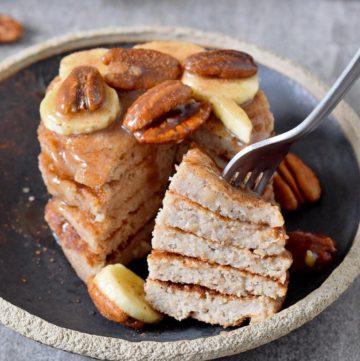 Gabel steckt in Pfannkuchen Turm mit Banane und Pekannüssen