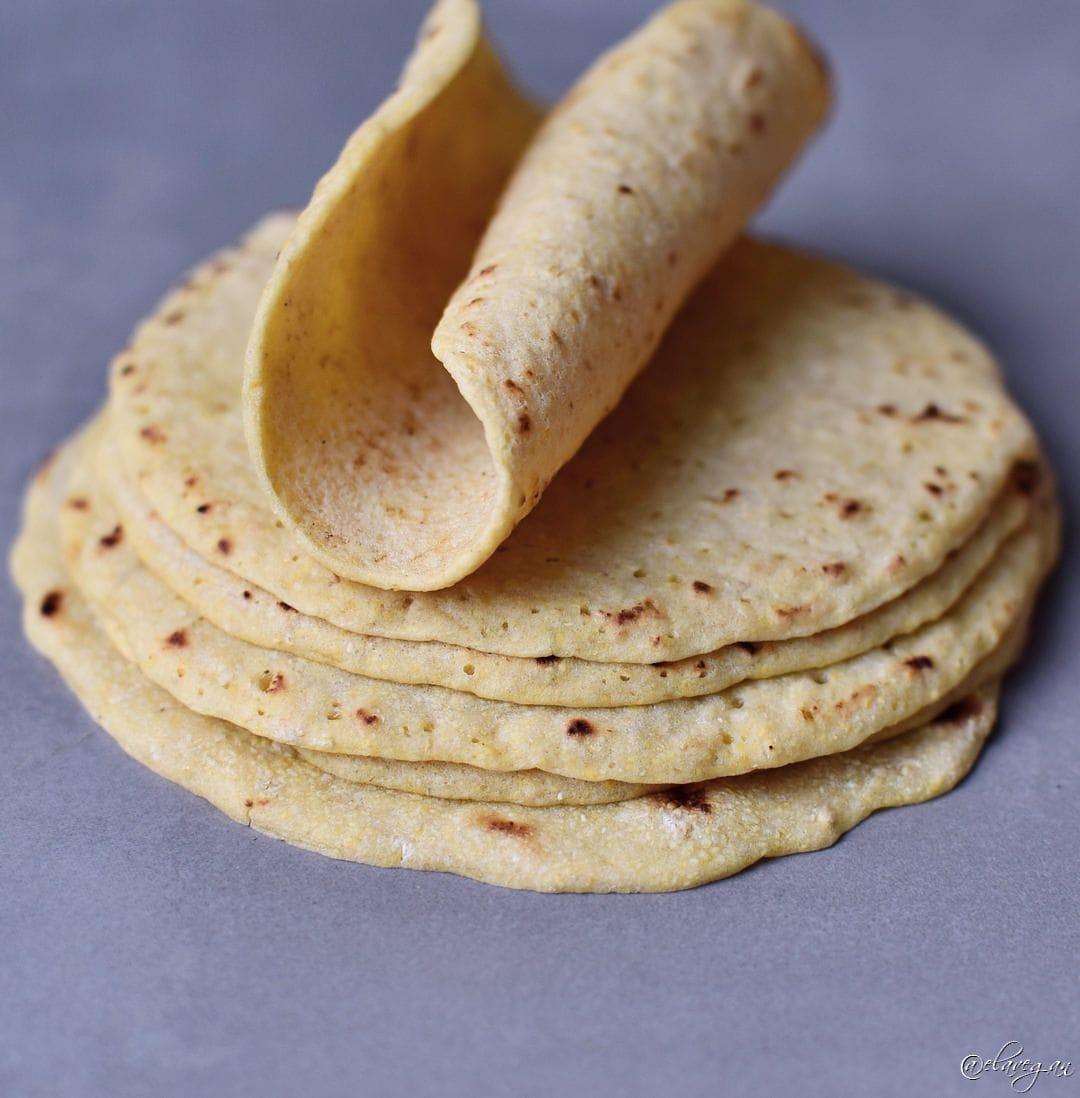 Eine aufgerollte selbstgemachte Tortilla auf einem Stapel von weiteren Tortillas