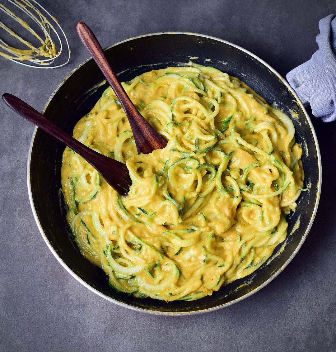 Zucchini Nudeln (Zoodles) mit veganer Käsesauce in schwarzer Pfanne mit Besteck