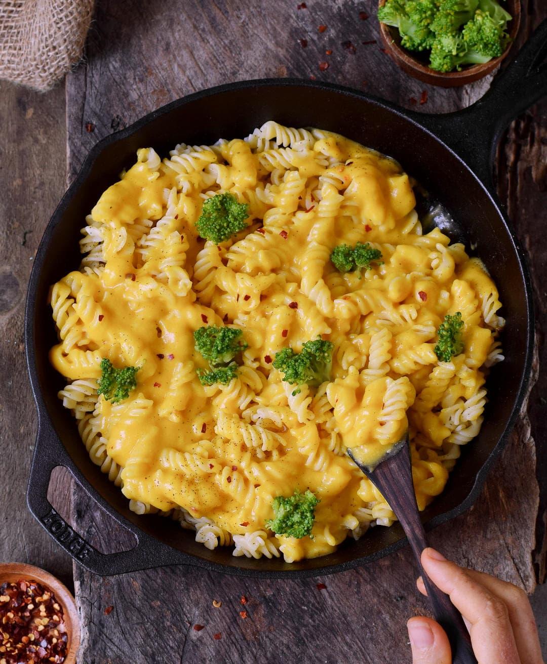 Vegan Mac n Cheese Käsesauce mit Nudeln und Brokkoli in schwarzer Pfanne