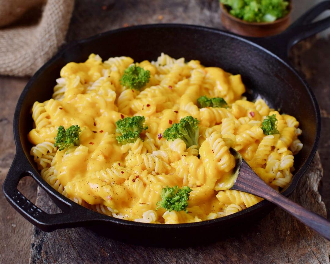 Gesunde vegane Mac n Cheese Käsesoße mit Nudeln und Brokkoli in schwarzer Pfanne