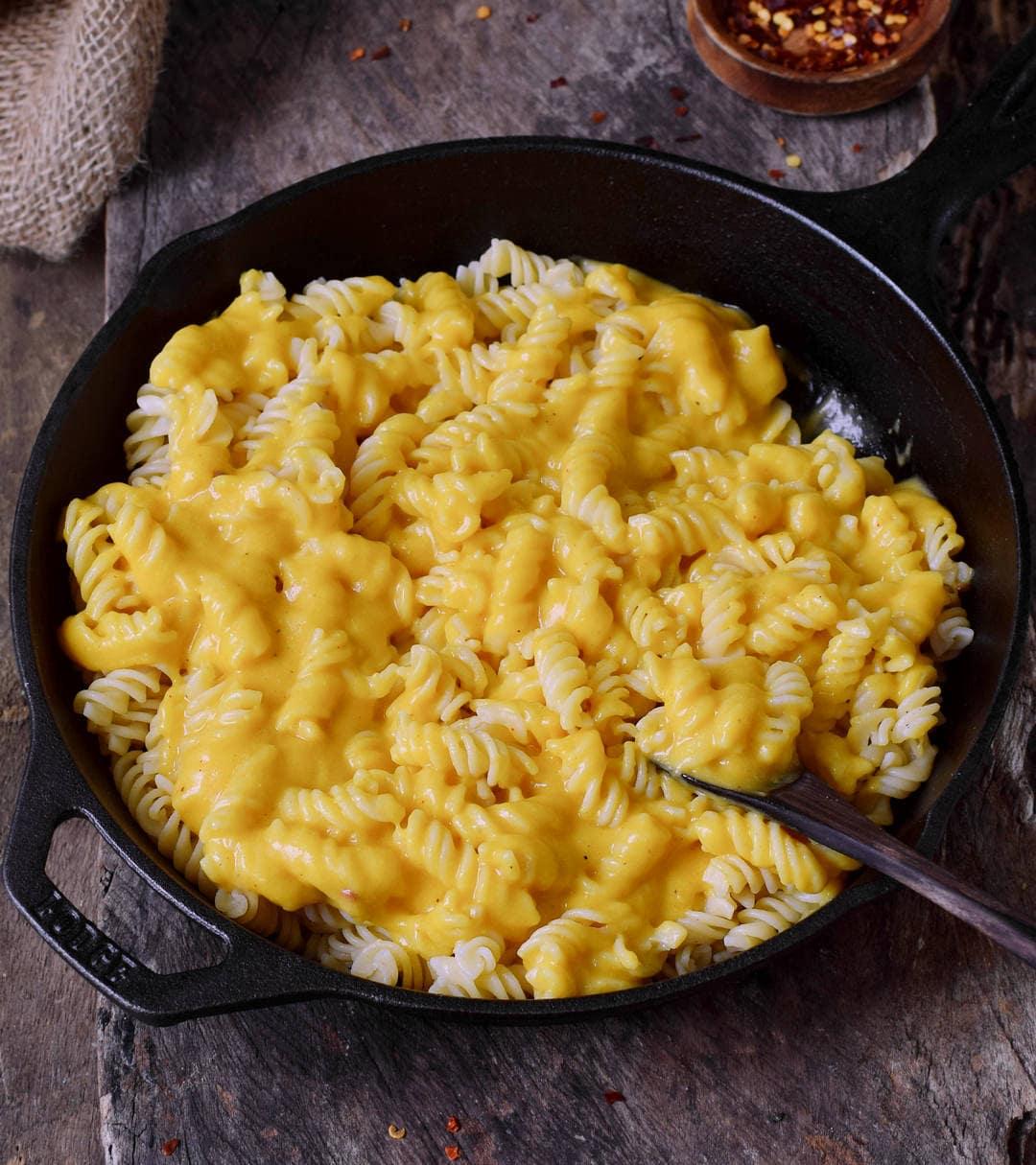 Vegane Käse-Makkaroni in schwarzer Pfanne mit Löffel