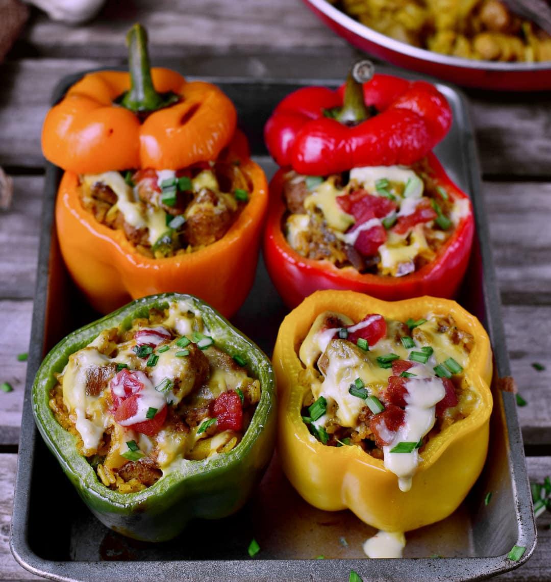 4 bunte gefüllte Paprikas mit gesunden veganen Zutaten