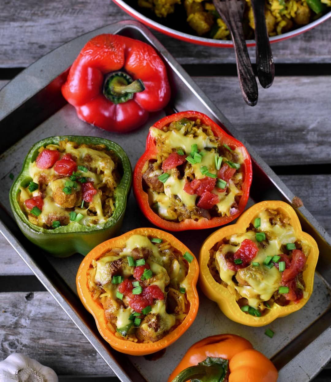 Paprikaschoten mit Gemüsefüllung, Reis und veganem Käse von oben