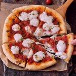 Glutenfreier Pizzateig belegt mit Tomatensoße und Mozzarella