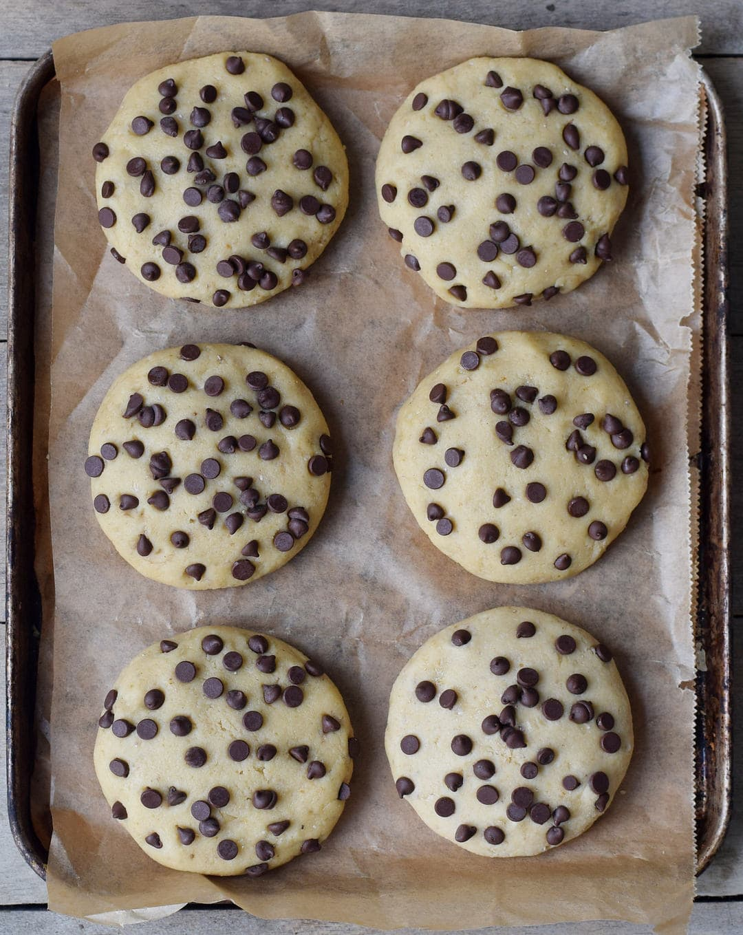 6 ungebackene vegane Kekse mit Schokodrops auf Backblech