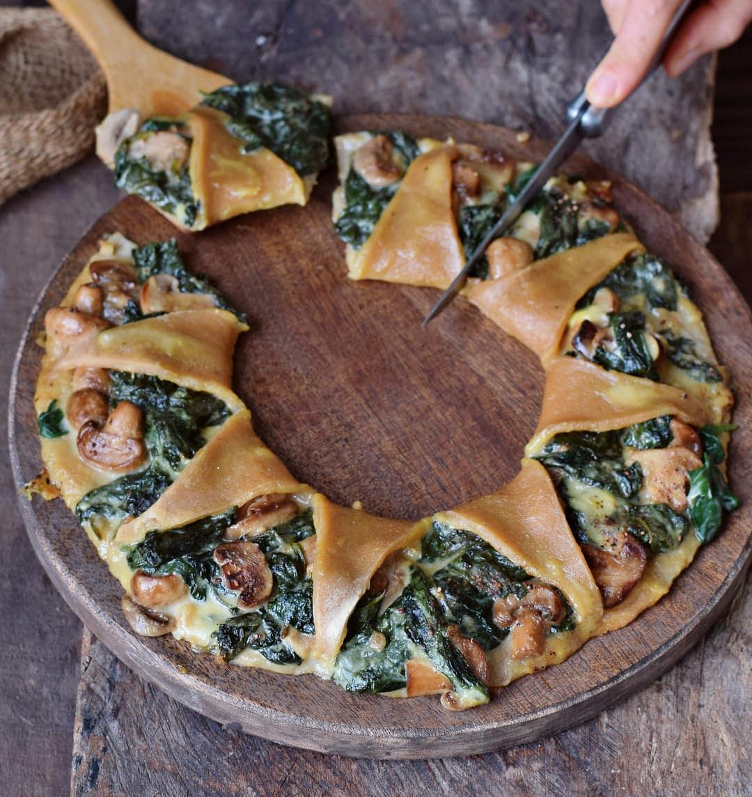 Schneiden von Pizzakranz mit Spinat Pilzen und veganem Käse