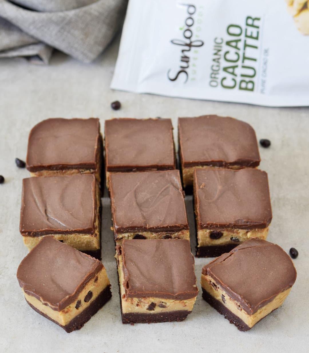 Vegane und glutenfreie Cookie Dough Brownies geschnitten mit Sunfood Kakaobutter Packung im Hintergrund