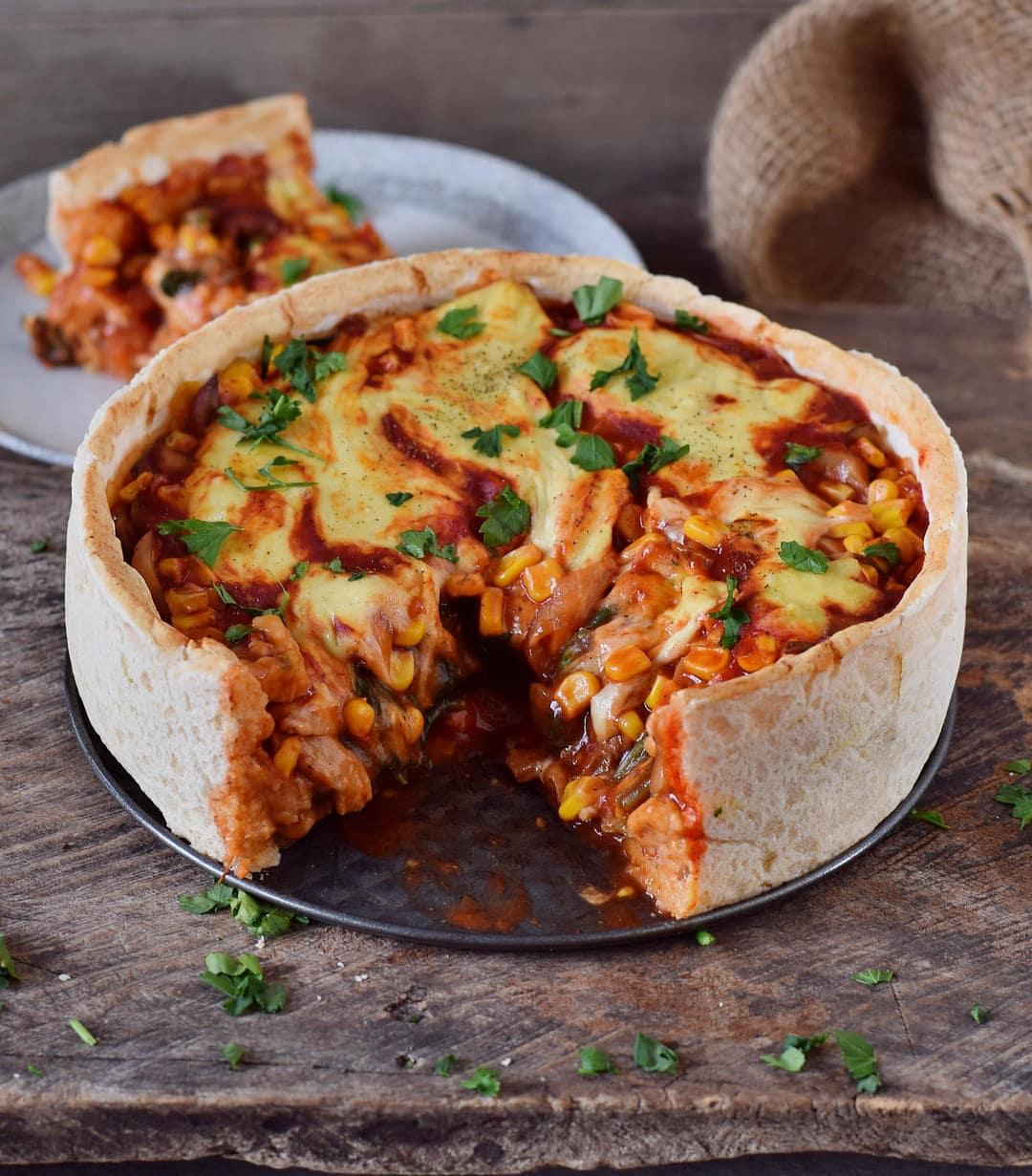 Veganer Pizza Kuchen aufgeschnitten mit Stück im Hintergrund