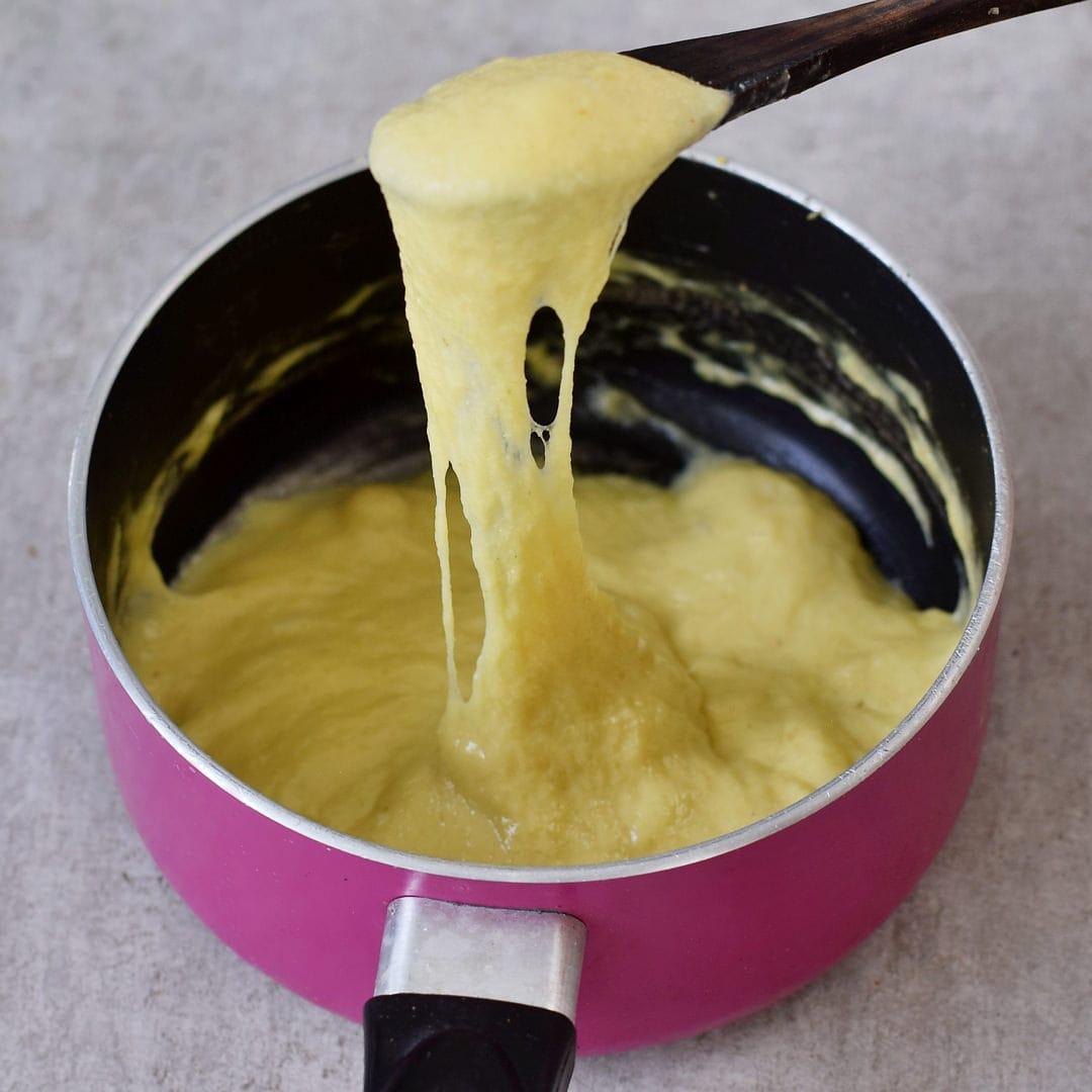 vegane Käsesauce in einem pinken Topf mit Holzlöffel