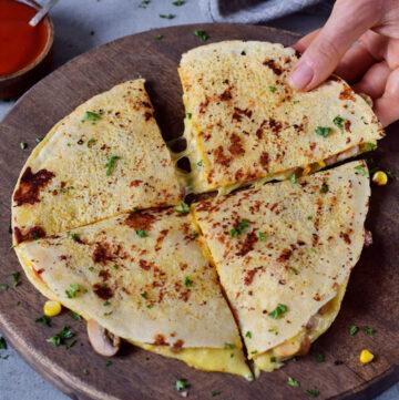 Hand greift nach Quesadilla auf Holzbrett gefüllt mit Käsesauce und Gemüse