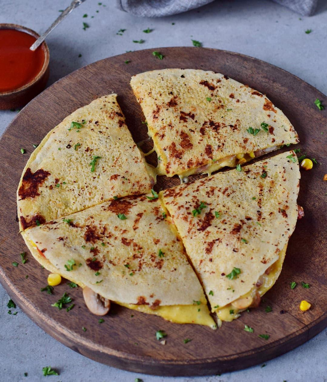 Vegane Quesadilla auf Holzbrett mit Käsesauce