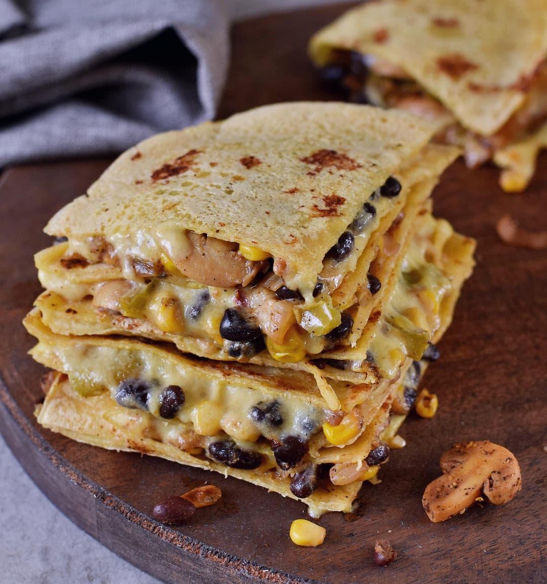 vegane Quesadillas gestapelt mit Käsesoße, schwarzen Bohnen und Gemüse gefüllt