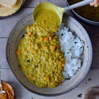 Linsen Dal mit Reis in Schüssel mit Kelle