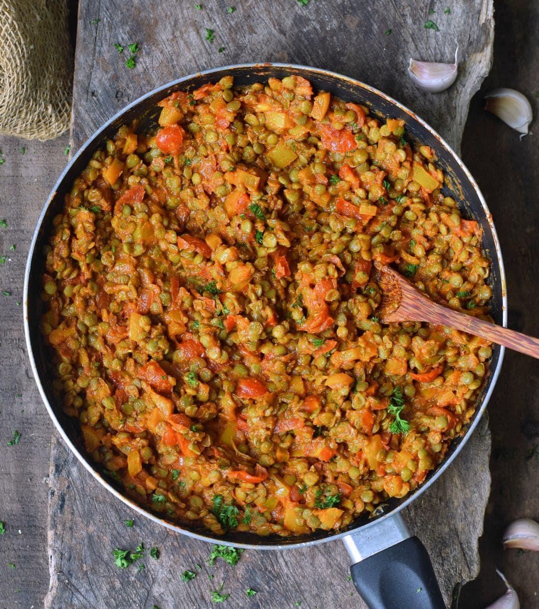 Pfanne gefüllt mit Linsen Gemüse und veganem Käse für Tortilla Schalen
