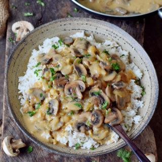 Pilz Stroganoff mit Reis in einer Schüssel mit Holzlöffel