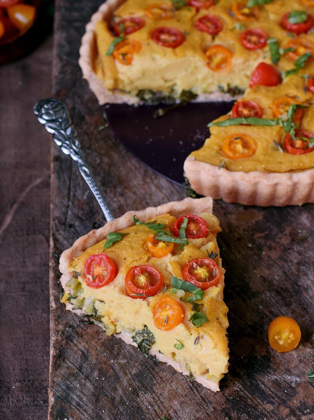 Ein Stück glutenfreie vegane Quiche ohne Eier mit Gemüse auf Tortenheber