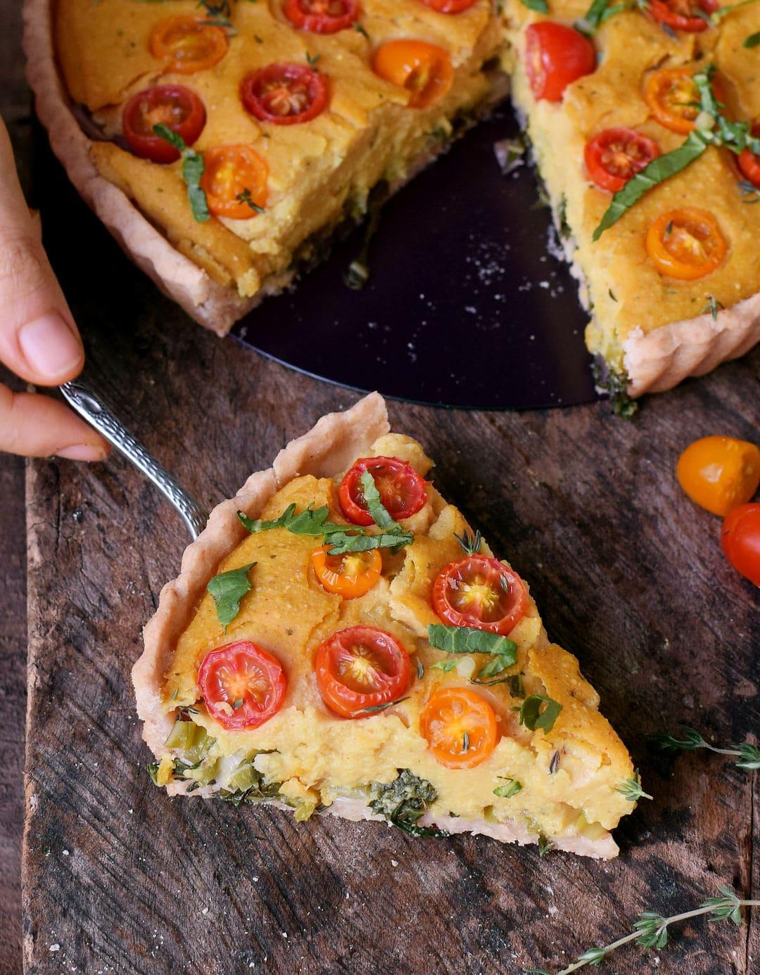 Ein Stück vegane Quiche ohne Eier auf Tortenheber