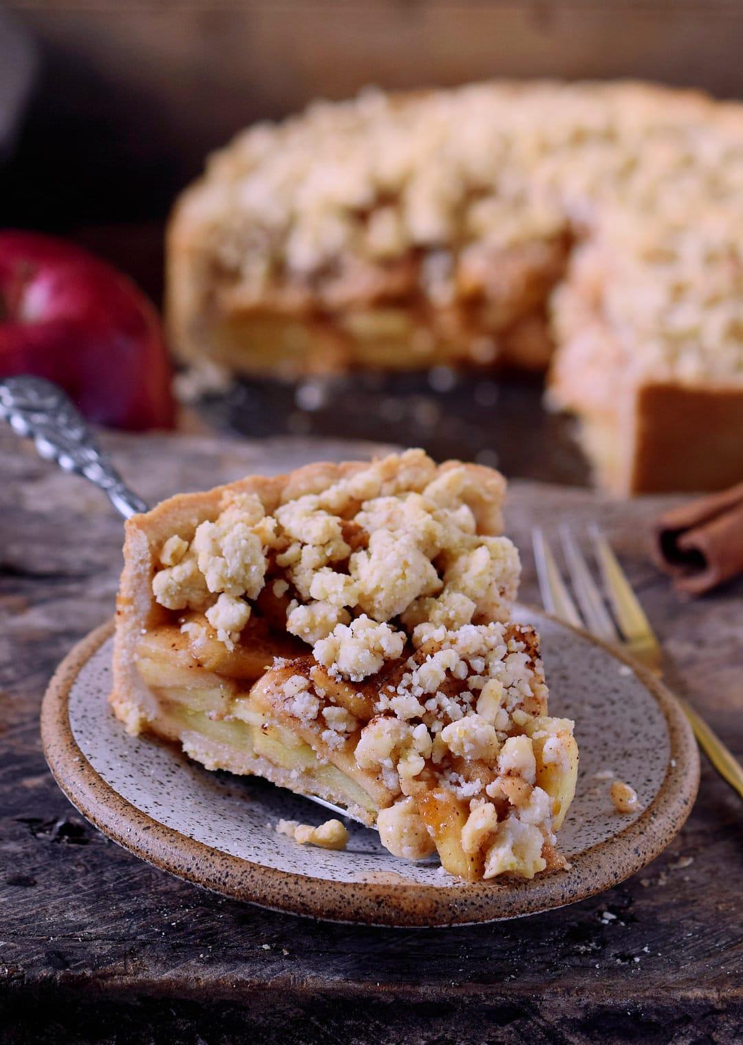 Ein großes Stück von veganem Apfel-Streuselkuchen auf einem Teller