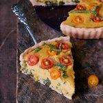 glutenfreie vegane Quiche (ohne Ei, ohne Soja) mit einem Stück auf Tortenheber