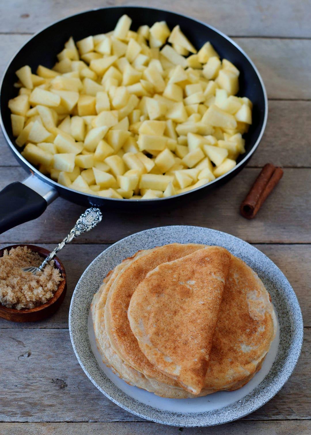 Äpfel in einer Pfanne und glutenfreie vegane Crepes auf einem Teller