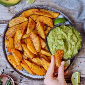 Knusprige Kartoffelspalten mit Guacamole auf einem Teller