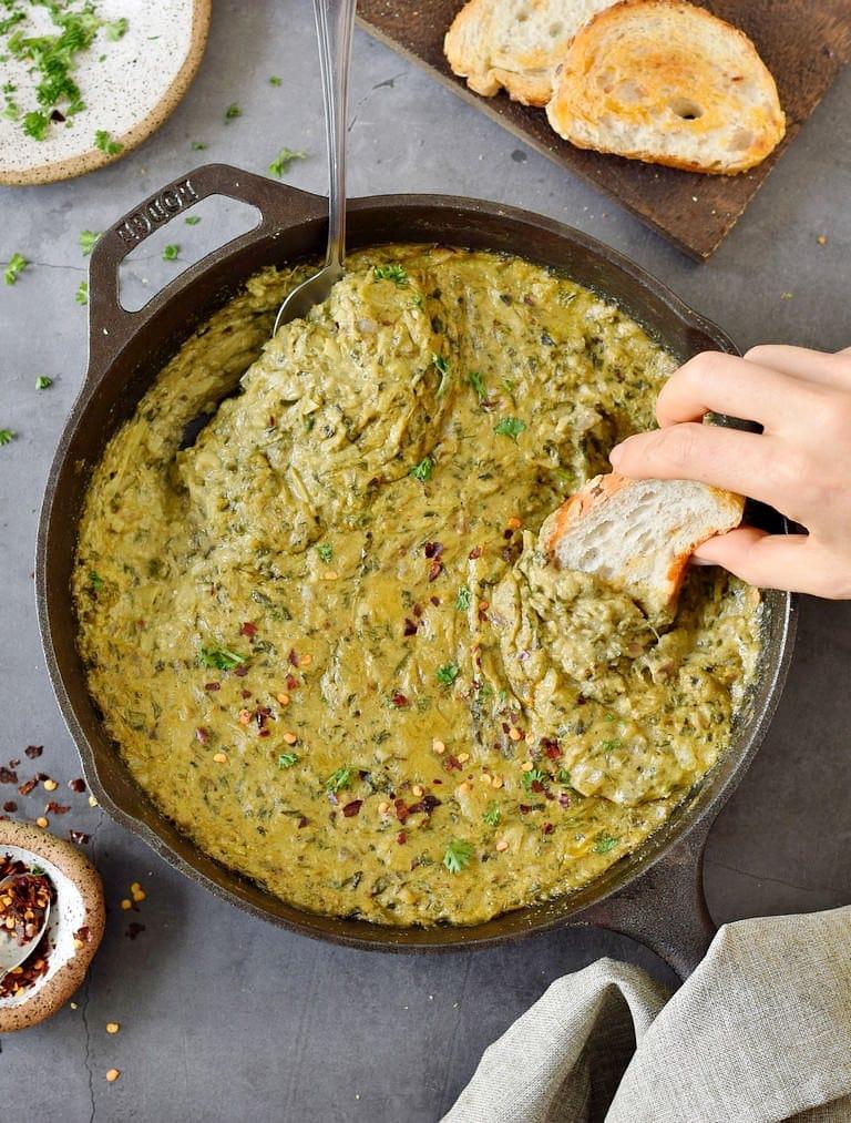 Hand taucht Baguette in einen veganen Dip
