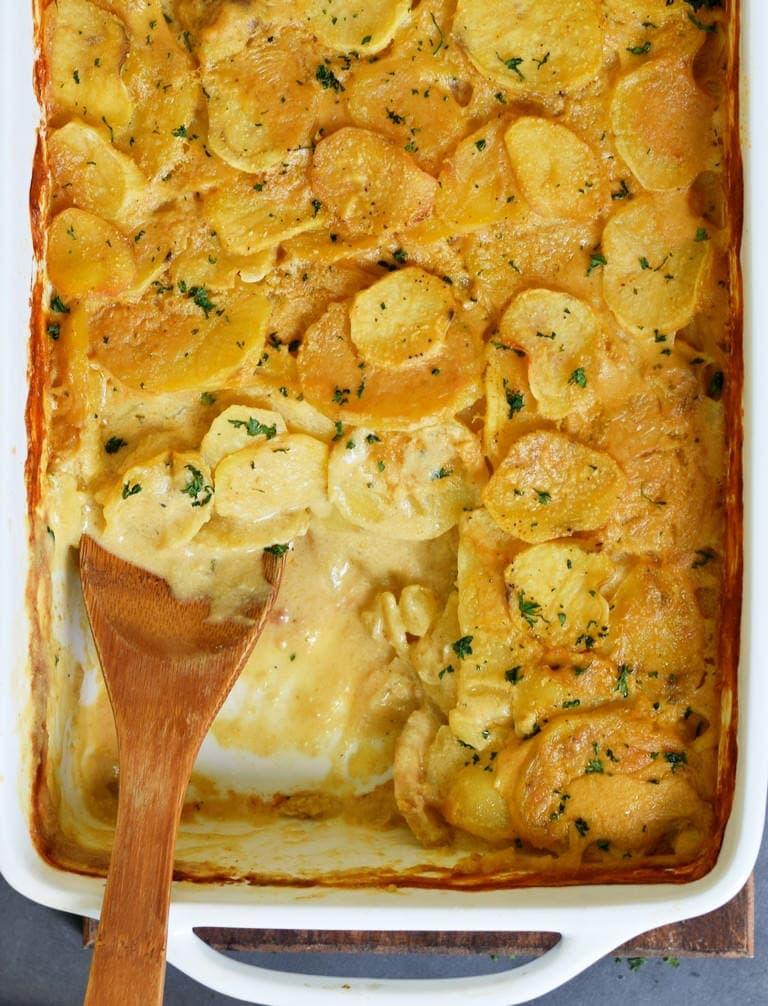Veganes Kartoffelgratin mit Holzlöffel in weißer Auflaufform
