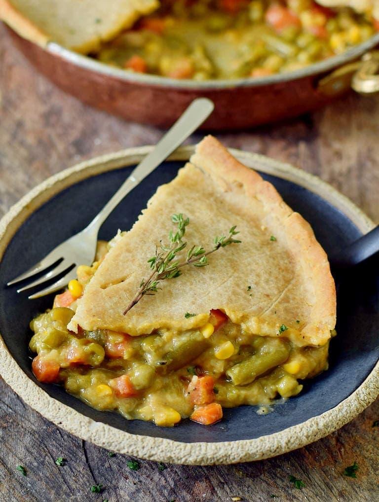 Ein Stück veganer Gemüsekuchen (Pot Pie) auf einem schwarzen Teller