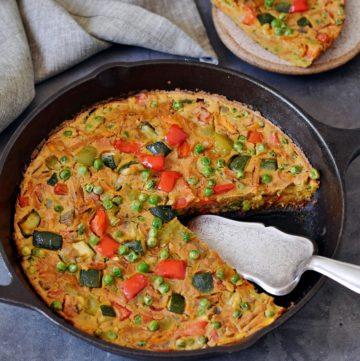 Gemüse Frittata in einer Pfanne mit Stück im Hintergrund auf Teller