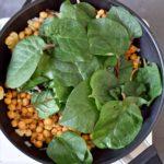 Kichererbsen und Spinat in schwarzer Pfanne