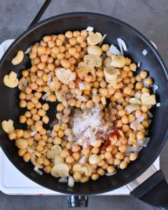 Kichererbsen und Zwiebeln in schwarzer Pfanne