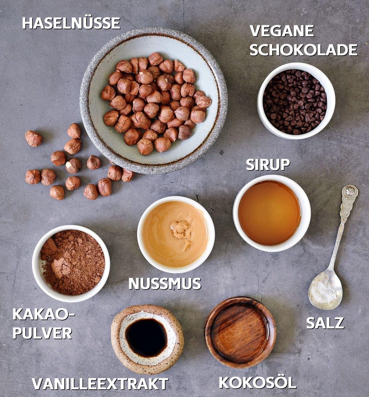 Vegane Schokolade, Sirup, Salz, Kokosöl, Nussmus, Vanilleextrakt, Kakaopulver, Haselnüsse auf grauem Hintergrund