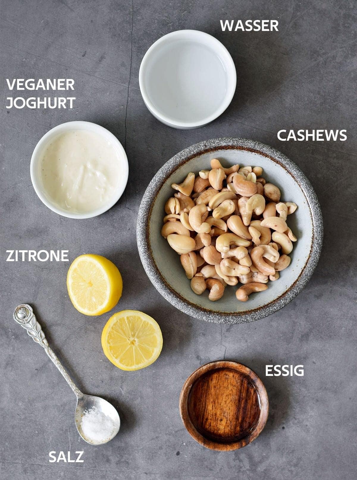wasser, cashews, essig, salz, zitrone, veganer joghurt auf graumen hintergrund