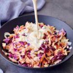 Veganes Dressing wird über Coleslaw (amerikanischer Krautsalat) gegossen