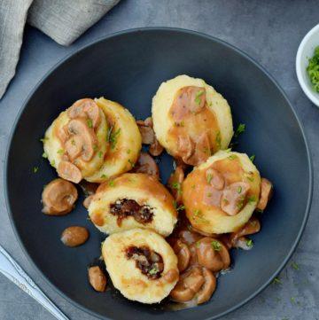 4 Kartoffelklöße in schwarzer Schüssel mit Pilzsoße