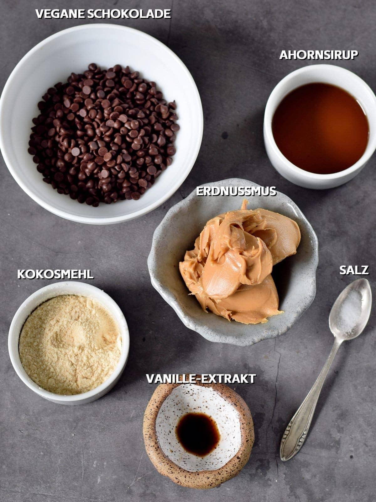 vegane schokolade, ahornsirup, erdnussmus, kokosmehl, vanille-extract, salz auf grauem hintergrund