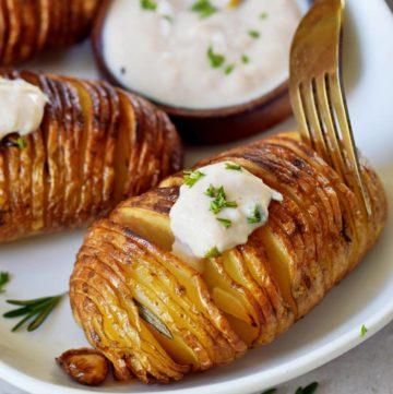 Gabel in Fächerkartoffel mit weißem Dip auf Teller