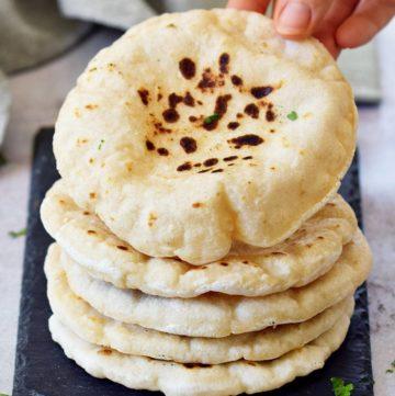 Hand greift nach einem Pita Brot Stapel