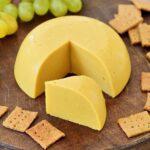 Bester veganer Käse (selbstgemacht) mit Crackern und Trauben auf rundem Holzbrett