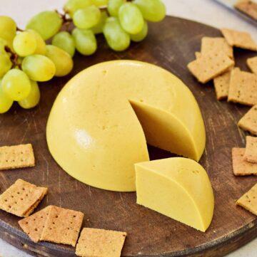 fester veganer Käse auf Holzbrett mit Crackern und Trauben