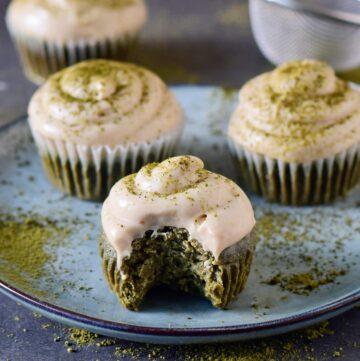 Vegane Matcha Cupcakes mit Frosting auf einem Teller und ein Stück angebissen