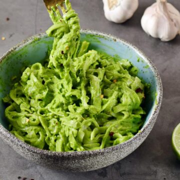 Grünkohl-Avocado-Nudeln in blauer Schale mit Gabel