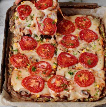 Hand greift nach einem Stück Low Carb Zucchini Pizza mit Tomaten und veganem Käse
