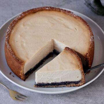 Veganer Kaesekuchen mit Mohnschicht auf weissem Teller