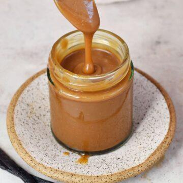 Karamellsoße im Glas mit Löffel darüber