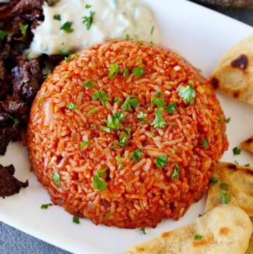 Tomatenreis mit Pita Gyros und Tzatziki auf weißem Teller
