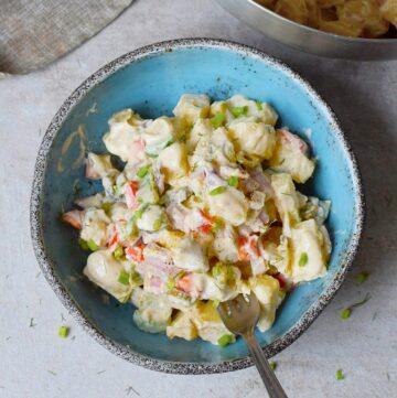 veganer Kartoffelsalat in blauer Schale mit Löffel