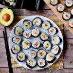 veganes Sushi auf weißem Teller von oben