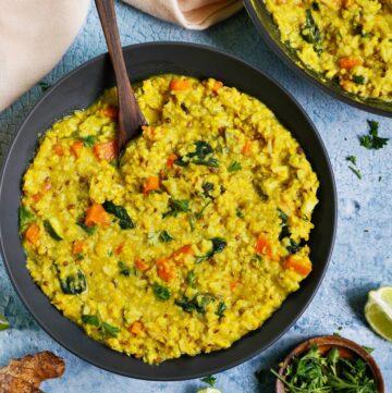 Kitchari mit Gemüse und Mung Dal in schwarzer Schale mit Löffel